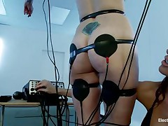 A sexy redhead with valuable boobs and a bald love tunnel is bound in front of this wicked brunette. Her body is overspread with electrodes and she's getting some stimulation through them and likewise from that fake penis the dark brown is using to rub her clitoris. Look at her moaning and receiving all the socking pleasures that babe wants.